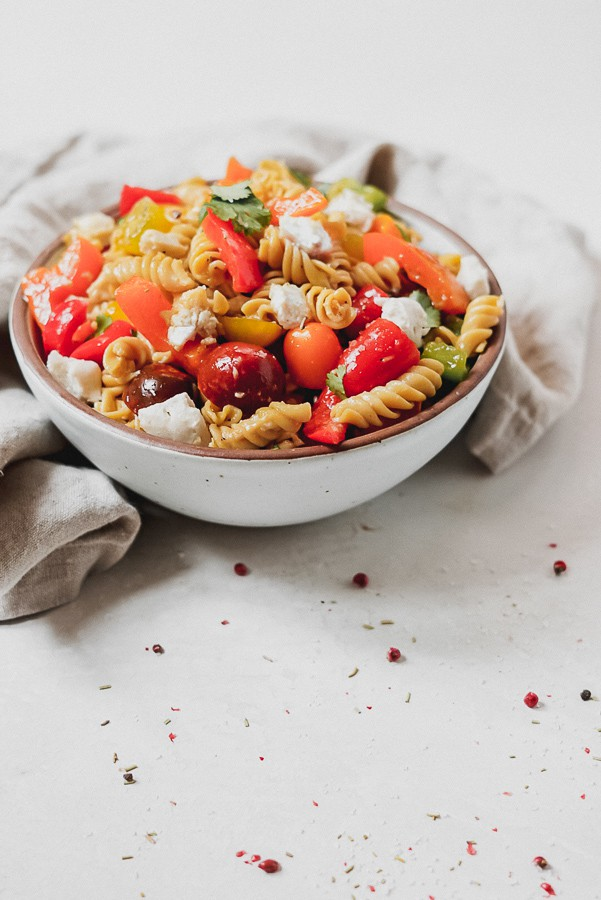 White bowl full of pasta salad with red peppers and tomatoes.