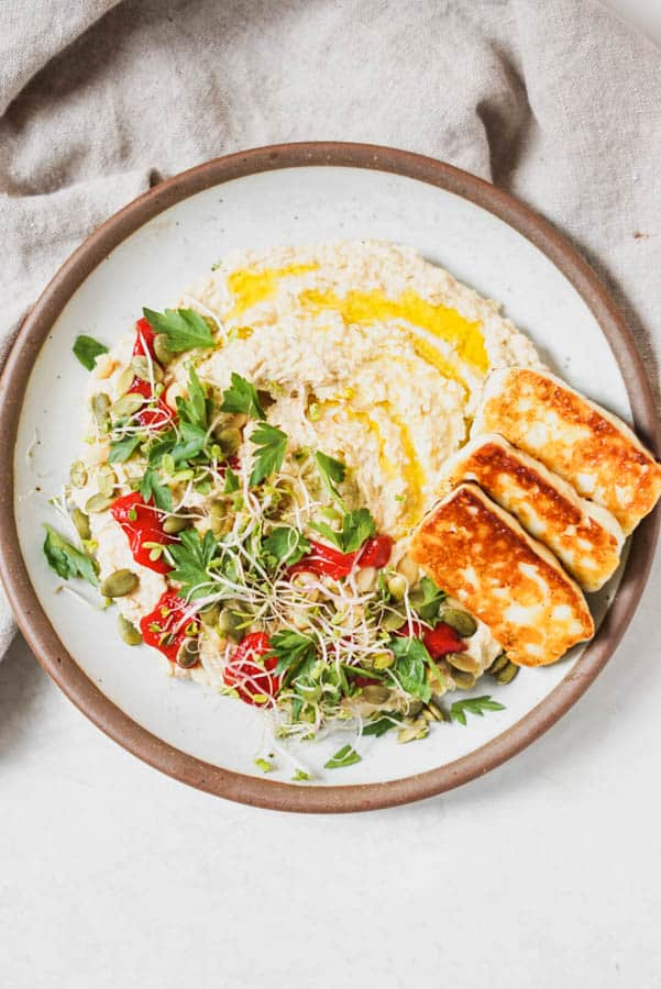 Hummus on a plate with toasted cheese and herbs.