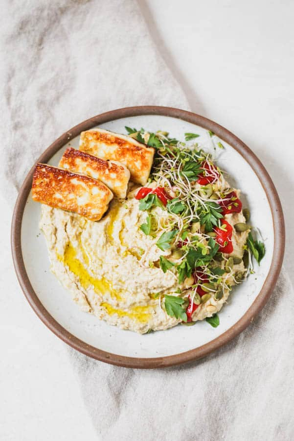 Brown plate full of hummus with herbs and cheese on top.